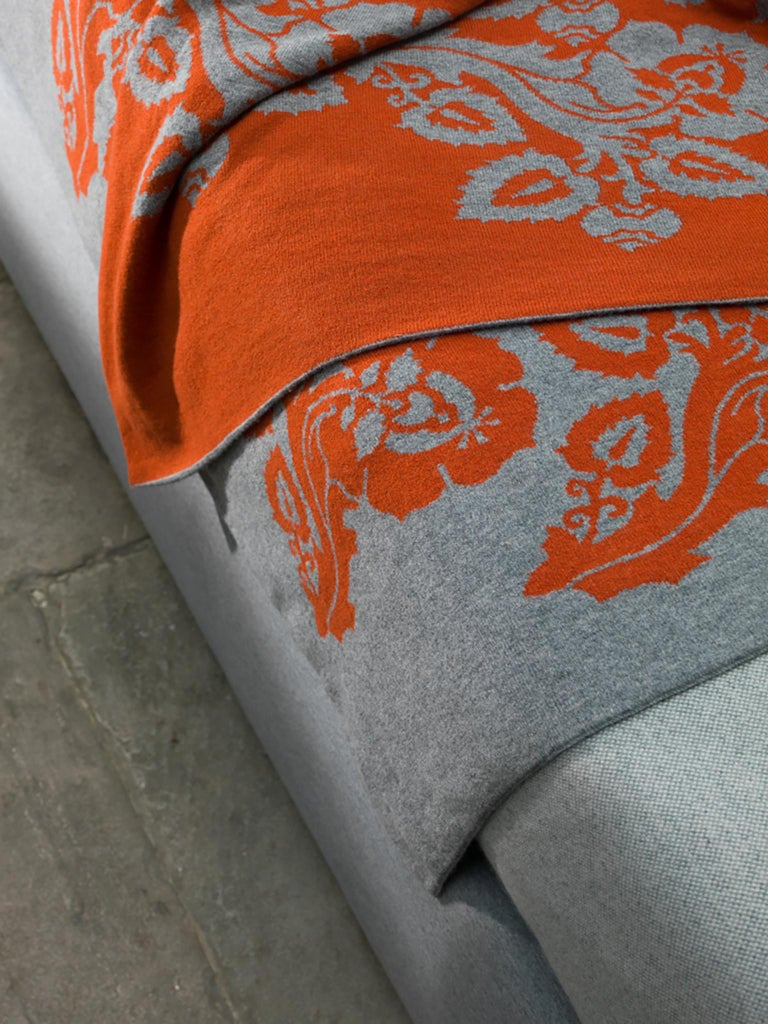This superb blanket is crafted of 100% soft cashmere. It was entirely handmade to create a sumptuous feel with a design reminiscent of traditional 16th century stylized floral motifs in grey, standing out over a deep crimson background. This