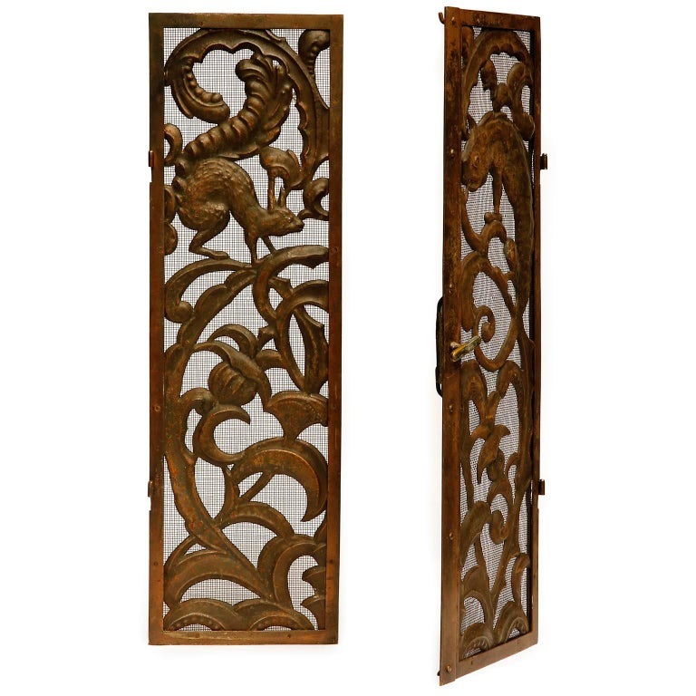 An antique and gorgeous pair of fireplace doors manufactured in Austria, circa 1900. The doors are made of a thin metal grid which are decorated with floral and figural ornaments and animals of hammered and patinated metal, brass or copper. The