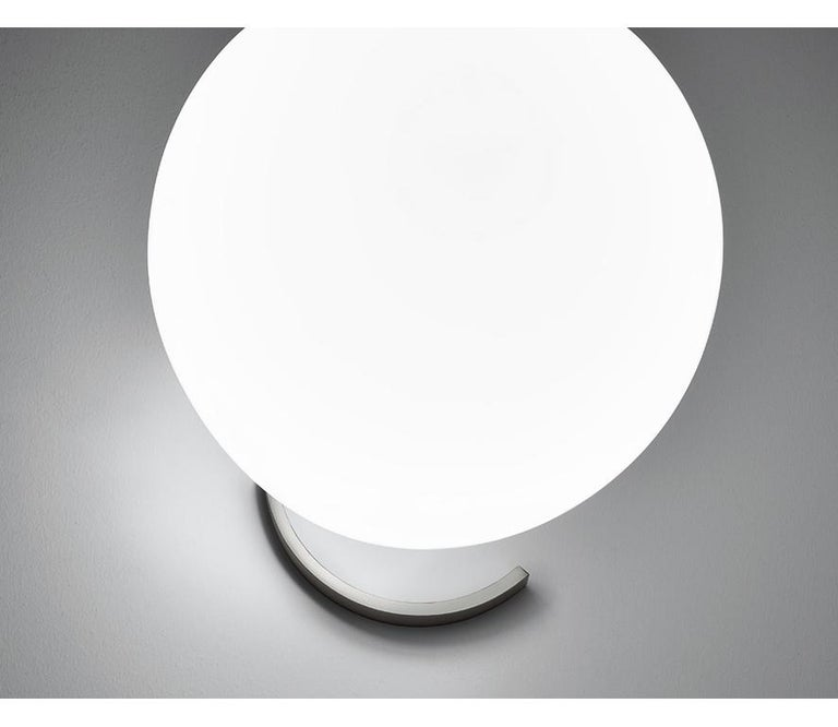 """Please note that VAT is not included in the price.  The only way to deceive gravity is balance"""" MDL Table lamp in two sizes distinguished by the opaline blown glass diffuser that seems to float in the empty space. Leaning on a steel structure in a"""