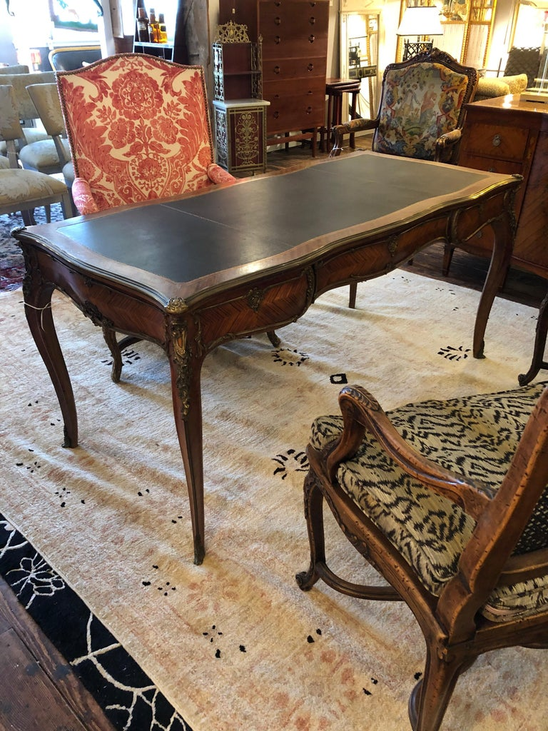 Exemplary early 20th century Louis XV style bureau plat with a top having a black gilt tooled leather insert framed by diagonal kingwood veneer frieze with 3 drawers outlined in scrolling gilt brass and Rococo escutcheons while Rococo foliage