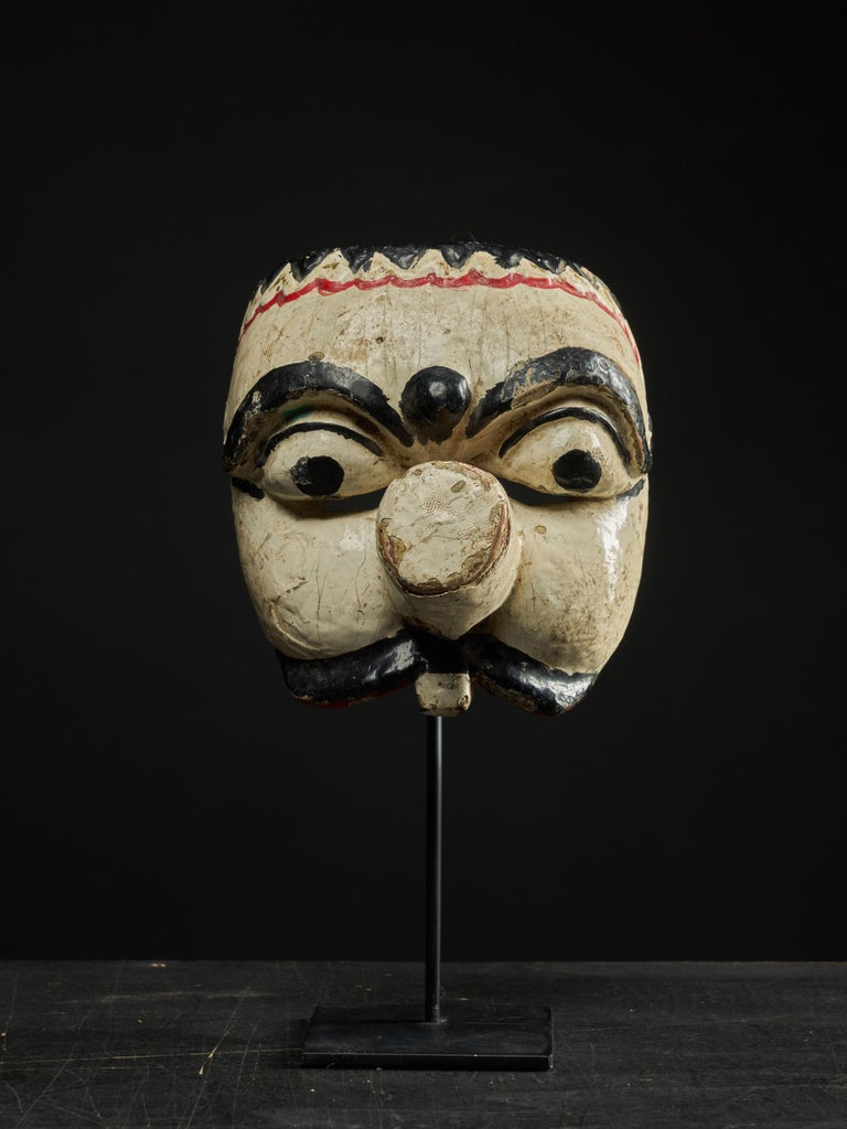 The mask is an example of traditional theater masks found in the cultures of Java, Indonesia. The face is carved out of wood and painted with colors that represent the status of the character. In this case, the mask is almost all white, which is a