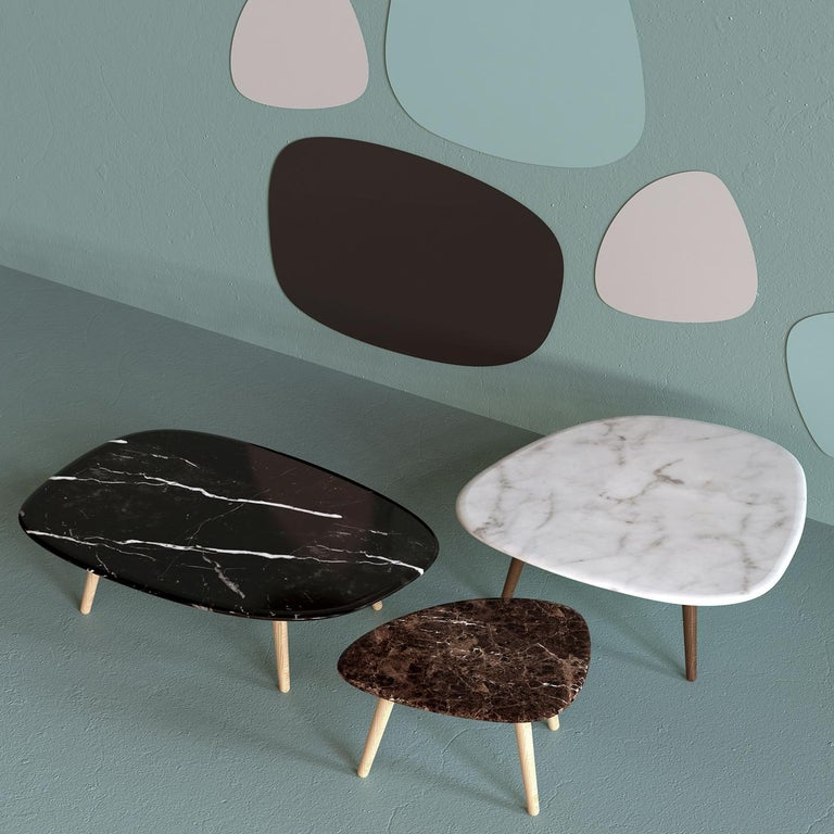 This sophisticated coffee table is characterized by a harmonious pairing of materials, combining a solid Emperador marble top with four natural oak legs for an understated yet rustic allure. Boasting an irregular silhouette with rounded edges, the