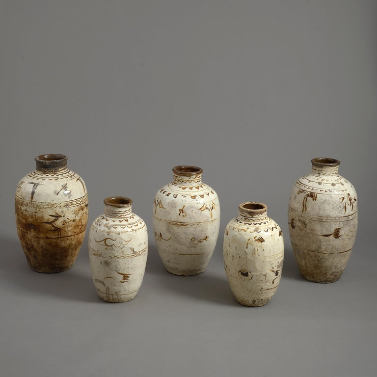 Five sixteenth century cream and caramel glazed Cizhou pottery vases.  Ming Period  Dimensions refer to tallest vase.