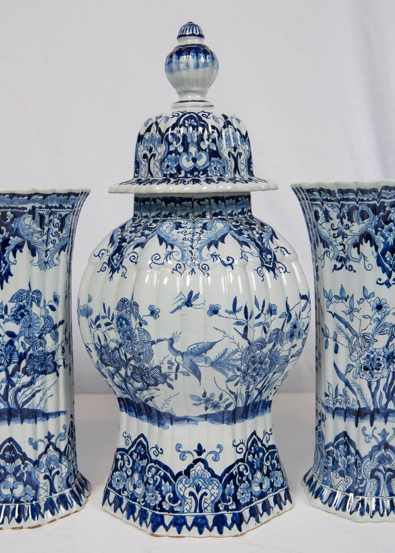A five piece French blue and white garniture in the style of delft made by the French company Samson et Cie, first quarter of 20th century. The vases are octagonal, and ribbed. The scene on the vases shows a bird in flight, and butterflies hovering