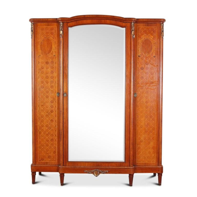 French Louis XVI-style inlaid satinwood bedroom suite, consisting of a 3-door armoire, a pair of matching nightstands, marble-top mirrored washstand, and a rare find - a queen-size bed frame. The pieces feature highly-detailed inlaid classical