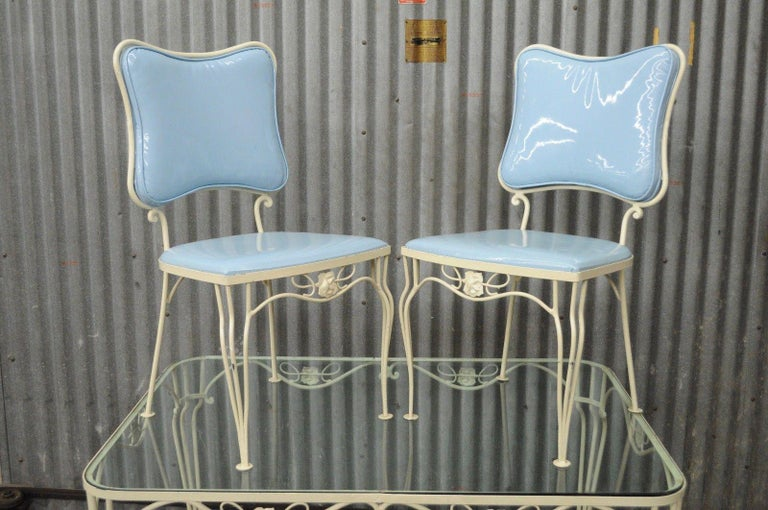 Vintage five-piece wrought iron patio dining set possibly by Woodard. Wrought iron construction, off-white painted finish, blue vinyl upholstered seat and backs, Floral rose accents, Rectangular rounded edge glass top table, four side chairs,