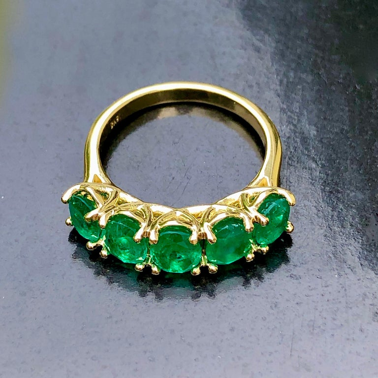 A classic emerald five stone ring. The graduated half-hoop of oval-cut Colombian natural emeralds, excellent color and clarity, highlighted with a scrolling gallery, mounted in 18K yellow gold. Victorian style, five stone rings were popular in the