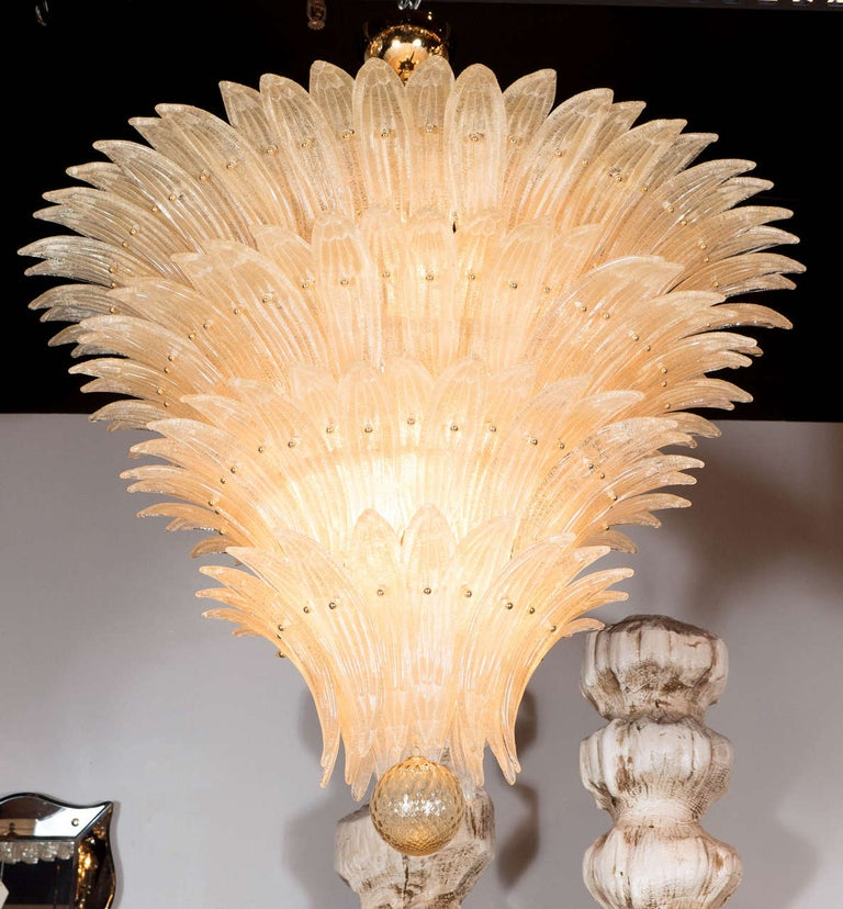 This exquisite Palma chandelier consists of five tiers of individually hand blown Murano glass stylized palm fronds in an iridescent Champagne color that are adhered to its brass frame in an alternating fashion on each tier that form a descending