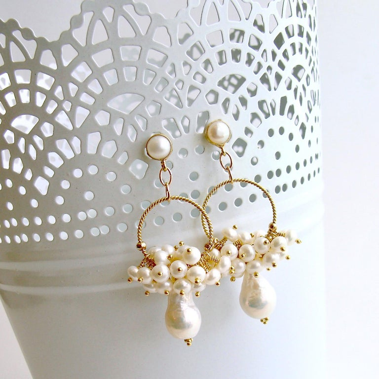 Hoop earrings seem to be the darling of Fall 2019/Winter 2020 and when paired with the timeless addition of pearls, this design is simply irresistible. A pair of organic flameball or neucleated pearl drops are adorned around a hoop with freshwater