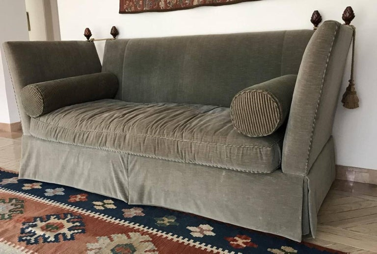 Elegant custom upholstered vintage sofa adorned with finials, tassels and pair of bolster pillows. Measures 46 x 88 x 39 inches. Upholstered in grey velvet with contrasting striped welt. This is a 1980s copy of the original style that dates back to