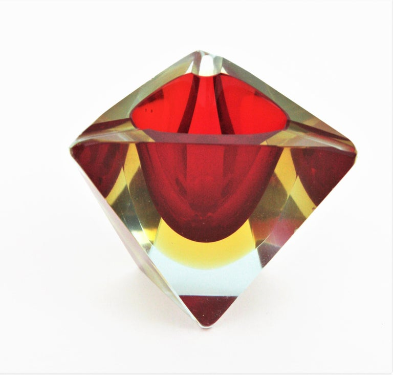 Sommerso faceted Murano glass triangular ashtray. Attributed to Flavio Poli, Italy, 1950s. Red and yellow glass cased into clear glass. It can be used also as small rings or jewelry bowl. Measures: 9 cm W x 8 cm D x 7 cm H.