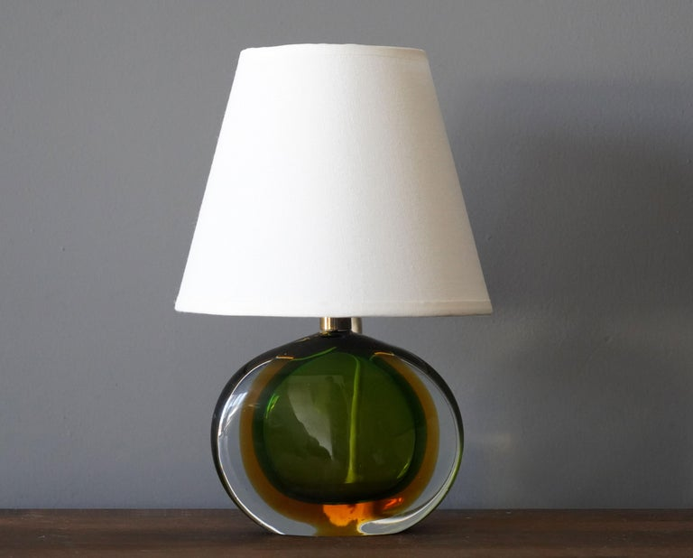 A small table lamp by Flavio Poli for Seguso. In green and orange colored Murano glass.  Other designers / makers of the period include Max Ingrand, Angelo Lelii, Josef Frank, Gino Sarfatti, and Fontana Arte.