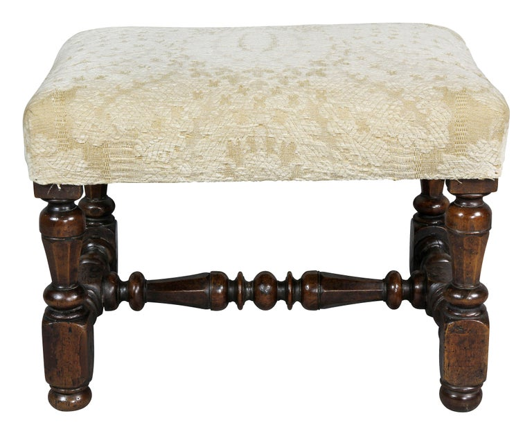 Rectangular upholstered seat with turned legs joining an H form turned stretcher. Button feet.