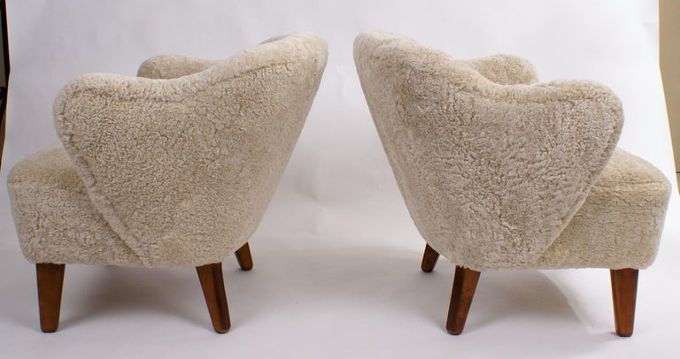 Flemming Lassen, pair of easy chairs for master cabinetmaker Jacob Kjaer, Denmark. Tapering legs in stained ash and reupholstered in beige sheepskin.