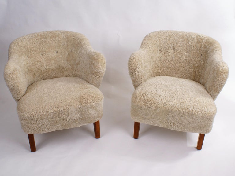 Flemming Lassen, pair of easy chairs for master cabinetmaker Jacob Kjaer, Denmark. Tapering legs in stained ash and reupholstered in pale grey colored sheepskin.  Please view 1stdibs item reference number LU108129189311 for a Flemming Lassen
