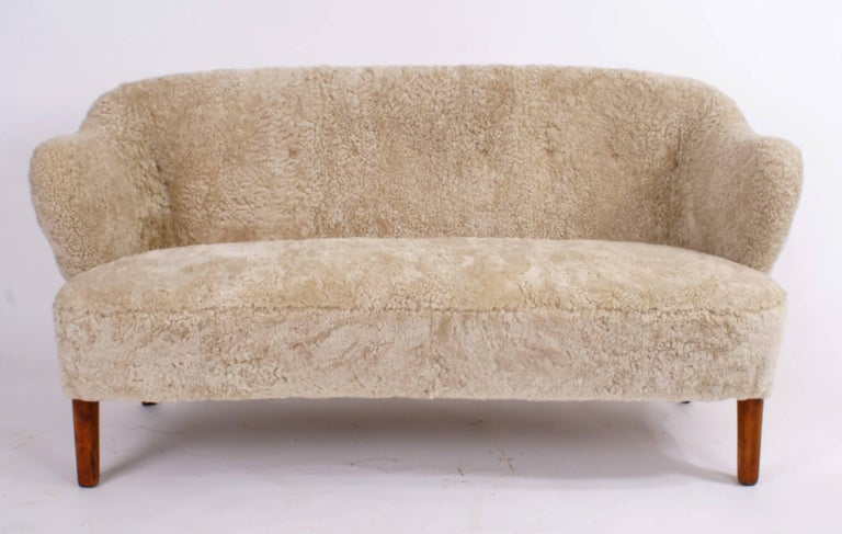Flemming Lassen, two-seat settee for master cabinetmaker Jacob Kjær, Copenhagen. Beige sheepskin upholstery and ash legs. Designed, 1940.  Please view 1stdibs item reference number LU1081219708072 for a pair of Flemming Lassen easy chairs that match
