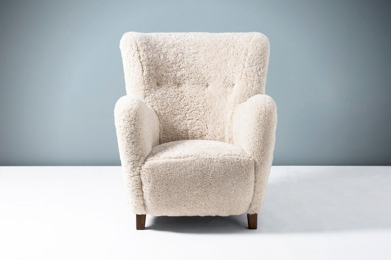 High-backed vintage armchair in the manner of Flemming Lassen, produced in Denmark sometime between 1940-1960. The legs are stained beech wood and the chair has been completely reconditioned in our London workshop with new upholstery in luxurious