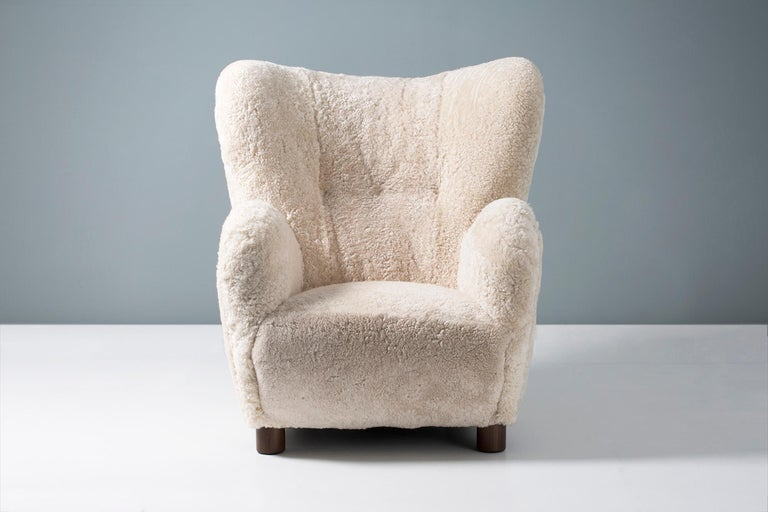 High-backed vintage armchair in the manner of Flemming Lassen, produced in Denmark sometime between 1940-1960. The legs are stained beechwood and the chair has been completely reconditioned in our London workshop with new upholstery in luxurious