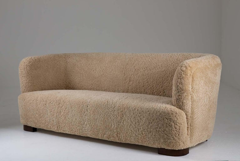 Stunning 3-seater sofa in the style of Flemming Lassen, manufactured in Denmark, 1930s.  This organically-shaped sofa is constructed with a very high sense of quality. The proportions are absolutely great with the soft, round shapes and low