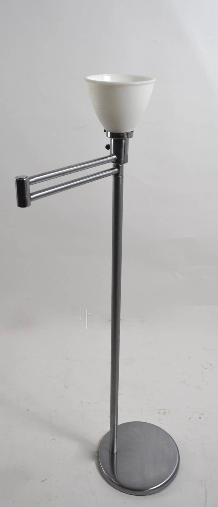 Classic flex arm floor lamp by Walter Von Nessen in clean, original, working condition. Iconic design, exceptional quality construction. Slight dents to base. Each segment of the swing arm is 12 inches (total extended length 24 inches). This