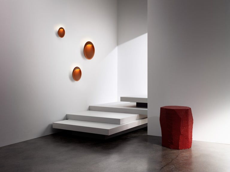 Large 'Flindt' indoor/outdoor wall light in Cortens Red for Louis Poulsen. A circular, wall-mounted fixture that brings bold, sculptural illumination to both indoor and outdoor spaces. The slim, elliptical lamp has a floating appearance that, paired