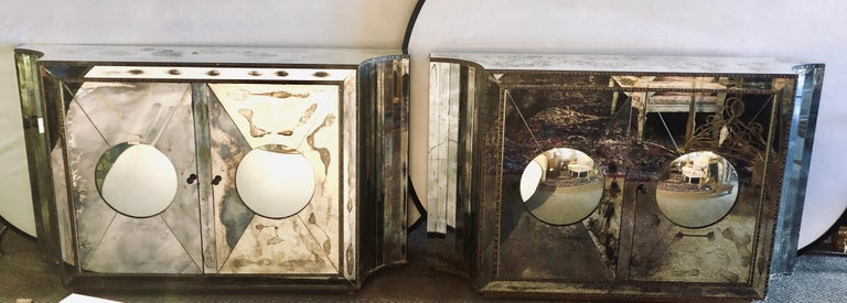 Pair of stunning one of a kind Art Deco rare concave sided with circular convex front double door all mirrored cabinets or console tables. The pair appear to be floating on air as they stand on distressed wooden carved hidden bases. Each having a