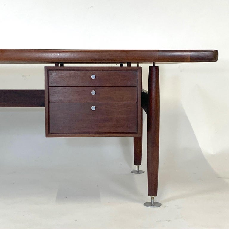A sleek leather topped walnut desk with a bank of drawers and machined pulls and oversized decorative glides by Lehigh Furniture attributed to Ward Bennett. Very impressive desk with some wear and patina to the leather but shows very well. Wood is