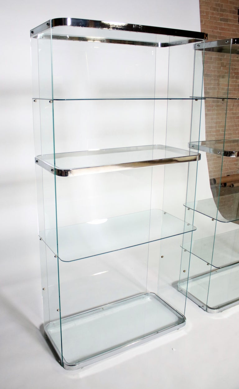 Pair of racetrack glass and polished chrome vitrines secured by glass back and side walls. Each unit holds up to 6 shelves - 11 are available. All metal and glass in excellent condition.