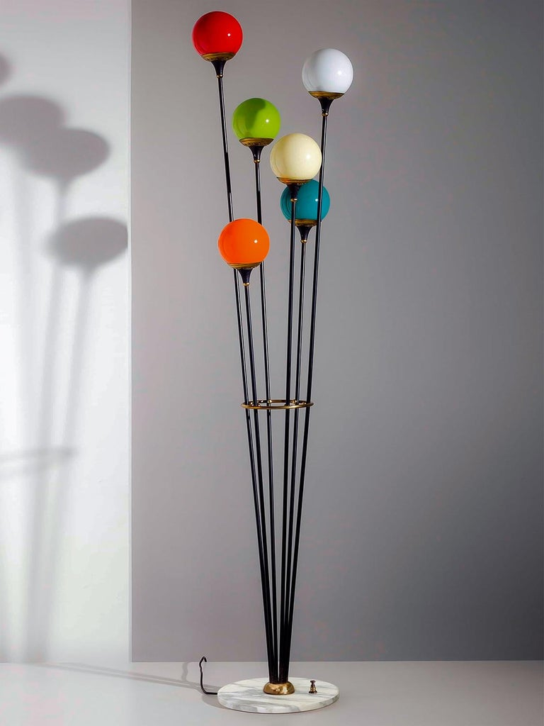 One of the most famous Stilnovo floor lamp six-lights, manufactured in Italy in the circa 1950. Marble round base, black metal structure with six colored blown Murano glass balls, mounted on brass lampshades. Its conditions of the period are to be