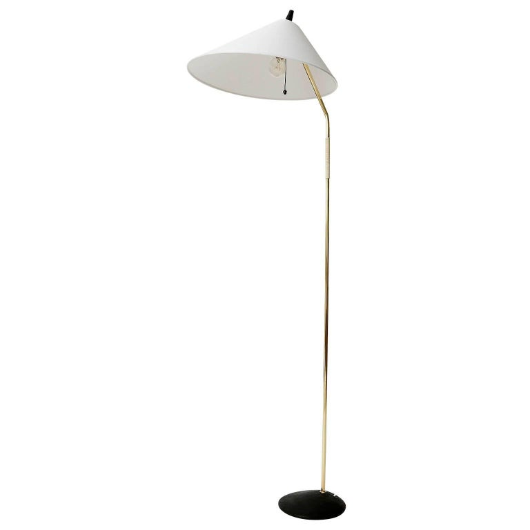 An Austrian brass floor lamp manufactured in midcentury, circa 1960 (end of 1950s or early 1960s). The fixture is attributed to Rupert Nikoll or J.T. Kalmar. The light is in excellent condition. It has been rewired, repolished and the natural