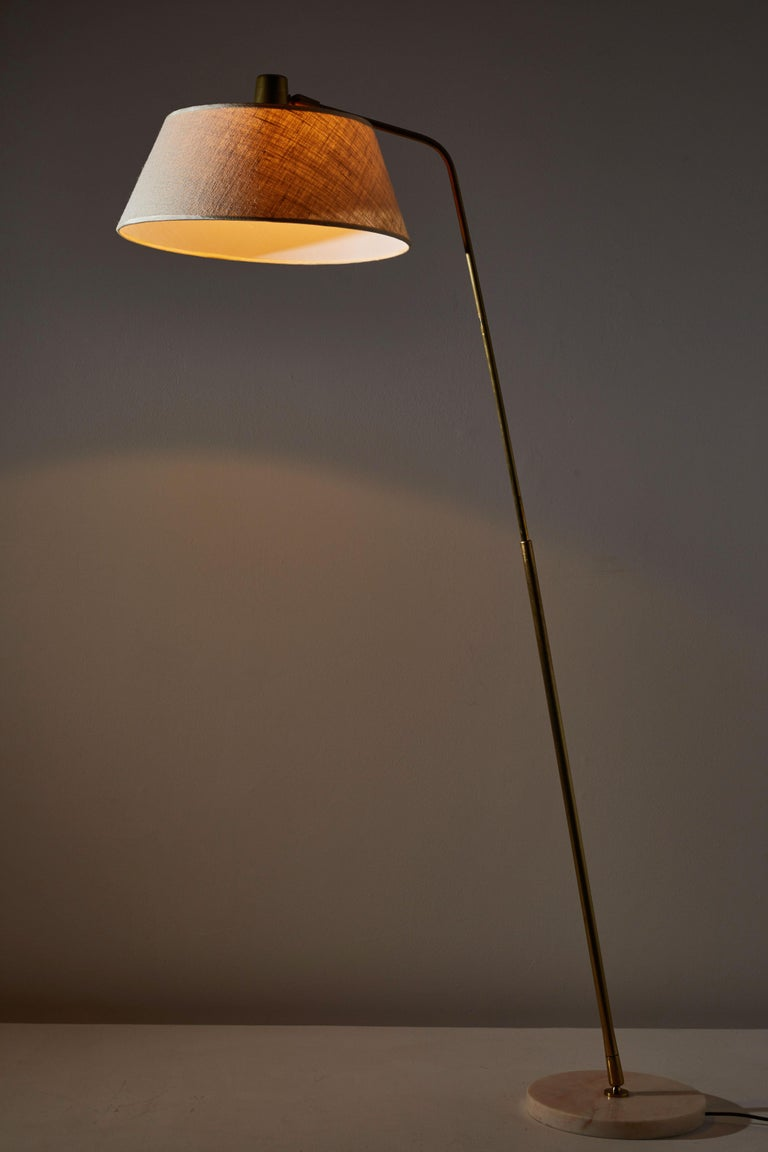 Floor lamp by Giuseppi Ostuni for Oluce. Designed and manufactured in Italy, circa 1950s. Brass, marble with custom linen shade. Stem adjust to various angles. Original cord with step switch. Takes on E27 75W maximum bulb.