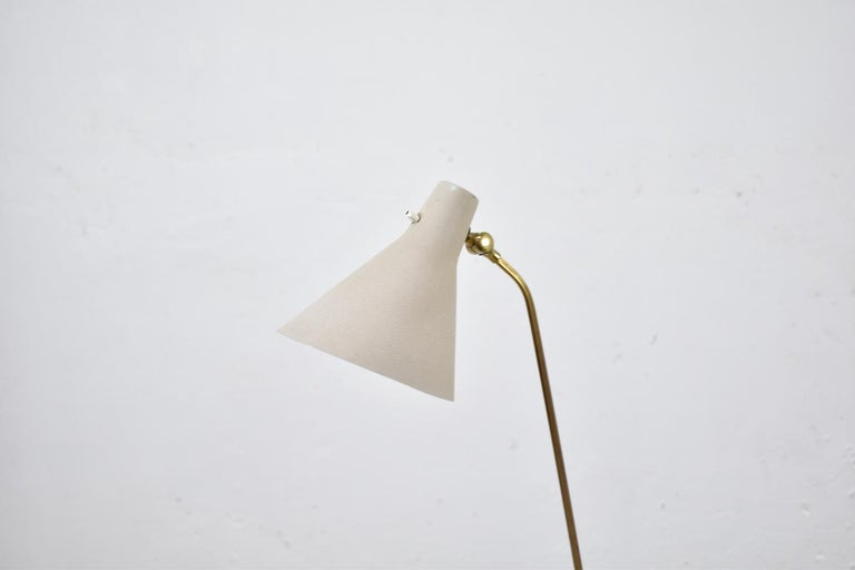 Lovely floor lamp designed by Hans Bergström and produced by Ateljé Lyktan, Sweden 1950s. This piece is made out of brass with lacquered metal and it features an adjustable nicely shaped lamp shade. Normally traces of age and use. Very rare!