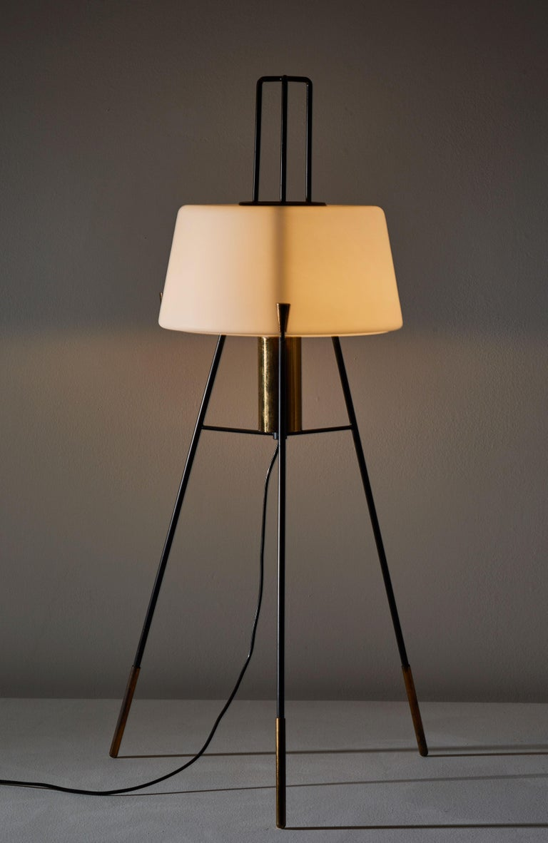 Floor lamp by Stilnovo. Manufactured in Italy, circa 1950s. Brushed satin glass diffuser, enameled metal tripod base, brass hardware. Original cord with brass step switch. Not wired for US, comes with adapter. Takes one E27 100w maximum bulb.
