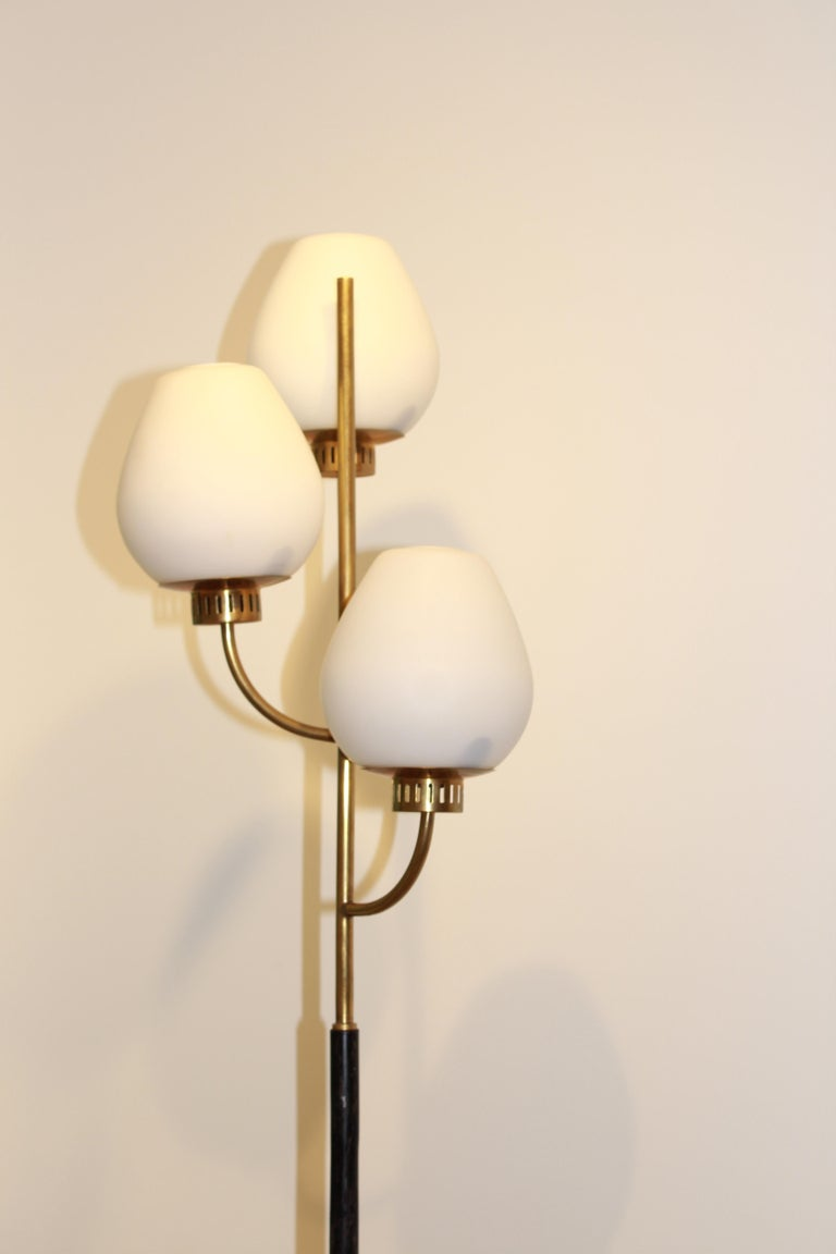 A floor lamp, 1950s. Marble, varnished tubular steel, brass, and frosted opaline glass.