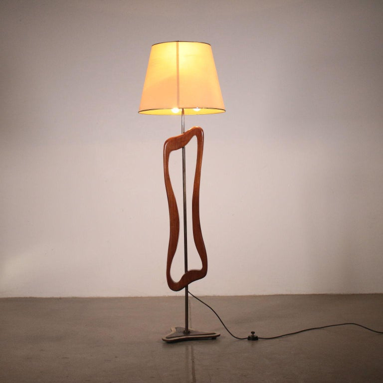 A floor lamp with fabric lampshade. Wood and brass. Manufactured in Argentine, 1950s.