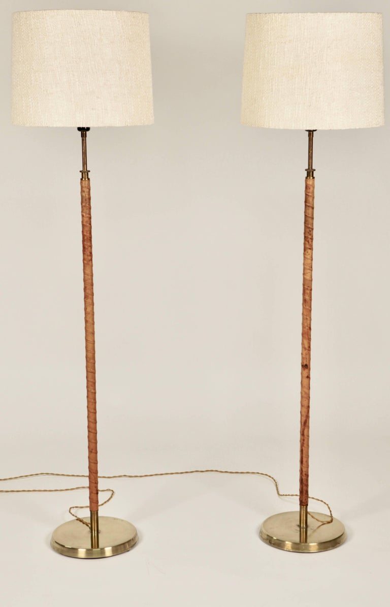 A pair of floor lamps, brass and natural leather with fantastic patina, raw linen shades.