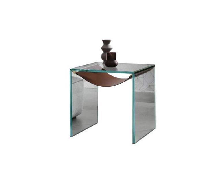 Side table with frame in extra clear glass. The shelf in leather is held by metal supports (stainless steel) distinguishes and completes the product.  Dimensions 19.6