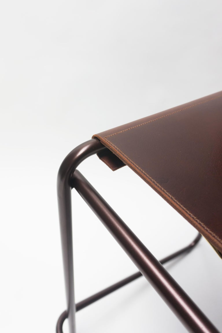 The Flora bar stool is composed of just three pieces of steel: an L-shaped back piece that touches the floor and rises up again at an angle to create a footrest, a rectilinear seat and front support, and a simple, stabilizing cross-bar across the