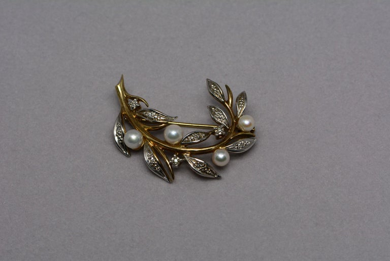 This vintage pearl brooch and earring set is made from white and yellow 9 karat gold, it has six cultured pearls and fourteen single cut diamonds set into it.  The brooch has four round cultured pearls and eight single cut diamonds which weigh: