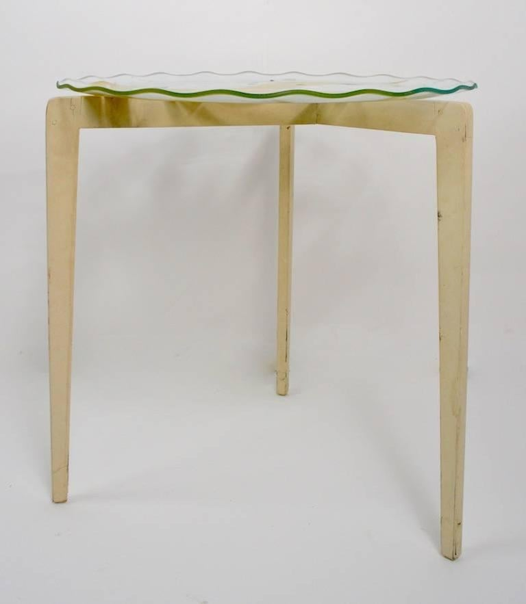 Two nesting glass top tables each having a circular form, wavy edge, reverse painted tops, which are attached to tripod wood bases. Both tables show cosmetic wear to finish, normal and consistent with age and use. Dimensions for larger table 25.5