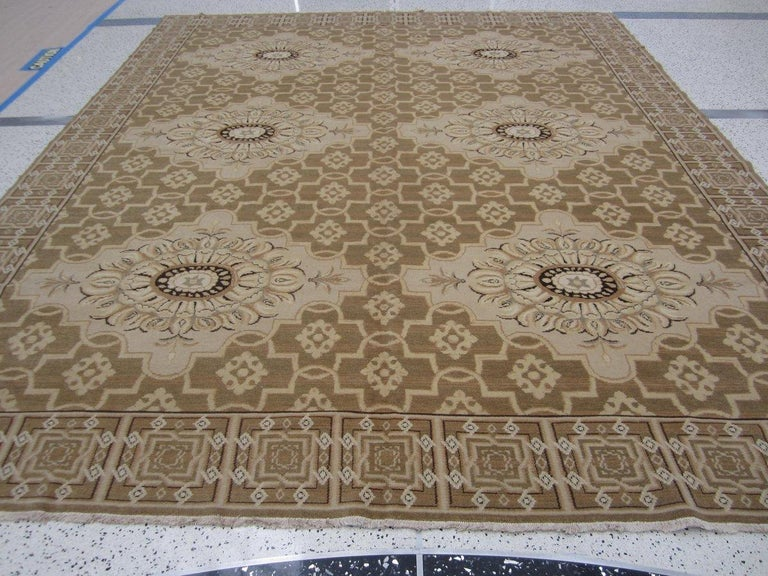 Floral medallions combine seamlessly with geometric patterns in a traditional rug of modern styling. Neutral tan and beige tones lend versatility without sacrificing style. Hand knotted wool.