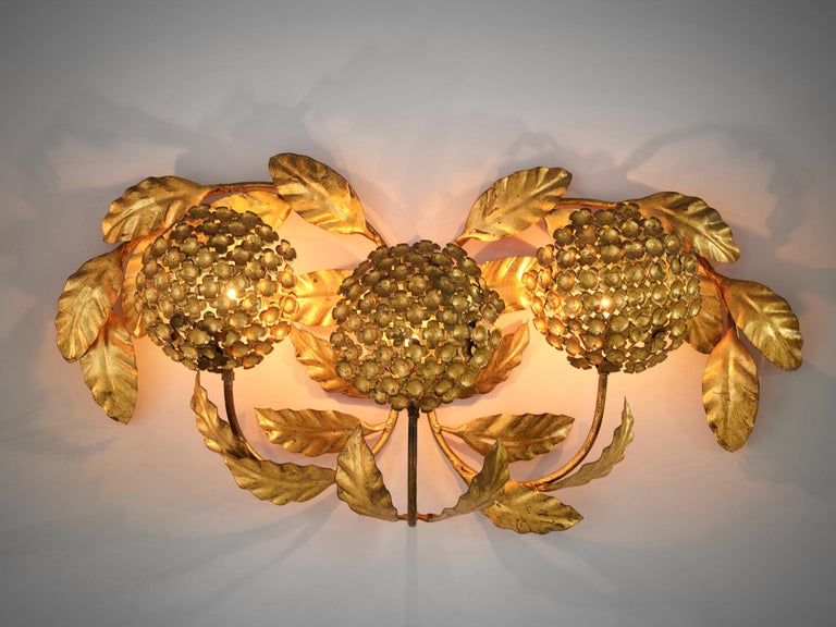 Floral wall light, brass, European, 1960s.  The lamp consists of three bulbs of flowers that diffuse the direct light. These bulbs protrude from the wall by their stems.The leaves that adorn the three bulbs get beautifully lit by the lamp, giving