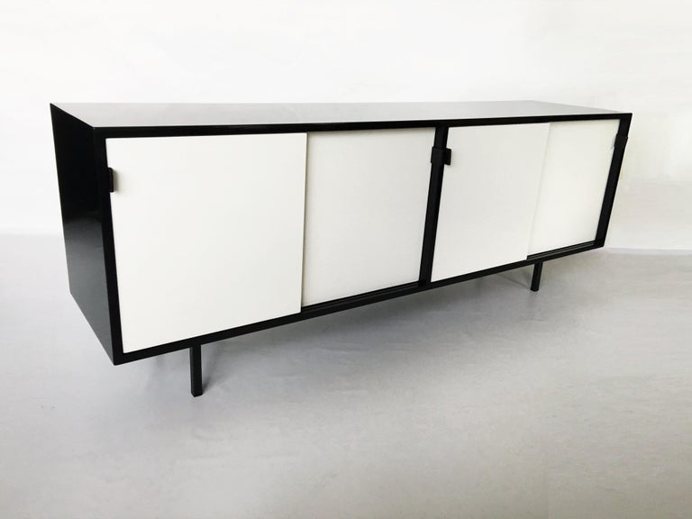 A modern take on the Classic, presented is an eye-catching black and white lacquered sideboard/credenza designed by architect and designer Florence Knoll and manufactured by Knoll associates inc, circa 1950s. The cabinet a features four sliding
