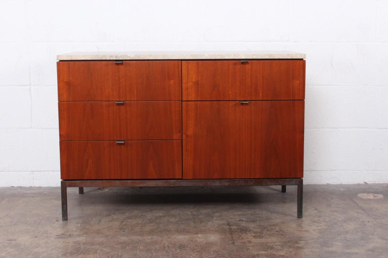 A walnut credenza with bronze base/hardware and travertine top. Designed by Florence Knoll for Knoll.