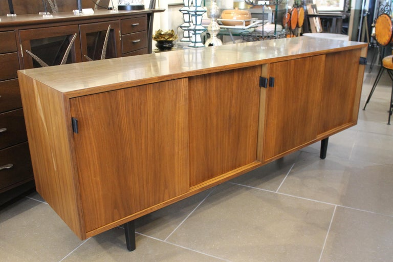 A Florence Knoll for Knoll Associates credenza, having a rectangular top above sliding doors with leather pulls and rising on tapered legs, with label verso. We replaced the leather pulls but, still have the original available.  We had the credenza