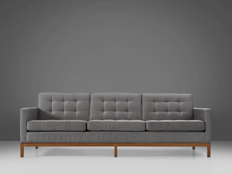 Florence Knoll for Knoll International, sofa model 2557, teak, fabric upholstery, United States, design 1955  Modern sofa with teak wooden base an grey fabric upholstery designed by Florence Knoll for Knoll International. The angular frame of the