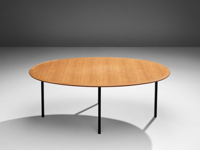 Florence Knoll for Knoll International, oval dining table, metal, teak,United States, 1950s  This table designed by Florence Knoll is based on four squared legs. These are made out of black colored metal that contrasts with the wooden tabletop. The