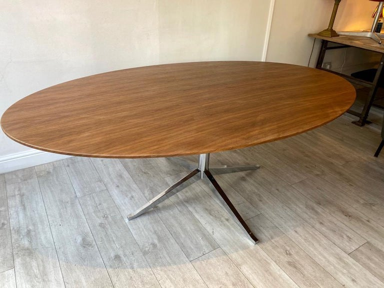 A beautiful walnut top oval dining table or meeting room table designed by Florence Knoll and manufactured by Knoll International.   This Classic Mid-Century Modern iconic table has a chrome base oval walnut top.  Makers mark on the foot of the