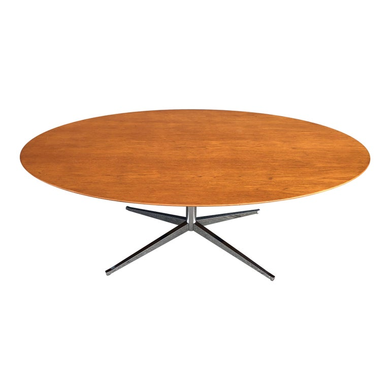 Up for sale is an iconic Florence Knoll oval table desk, on a sold chrome-plated steel four legged base. This particular table features a walnut top.   The table is in excellent condition. The wood top was just refinished, the is shiny with no