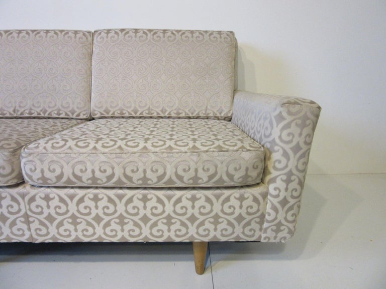 A three cushion sofa with inset wooden conical legs in clear birch with slanted arms and angled profile in a beautiful damask fabric with a bit of shimmer to the back round. A very early production piece model # 26 manufactured by Knoll.